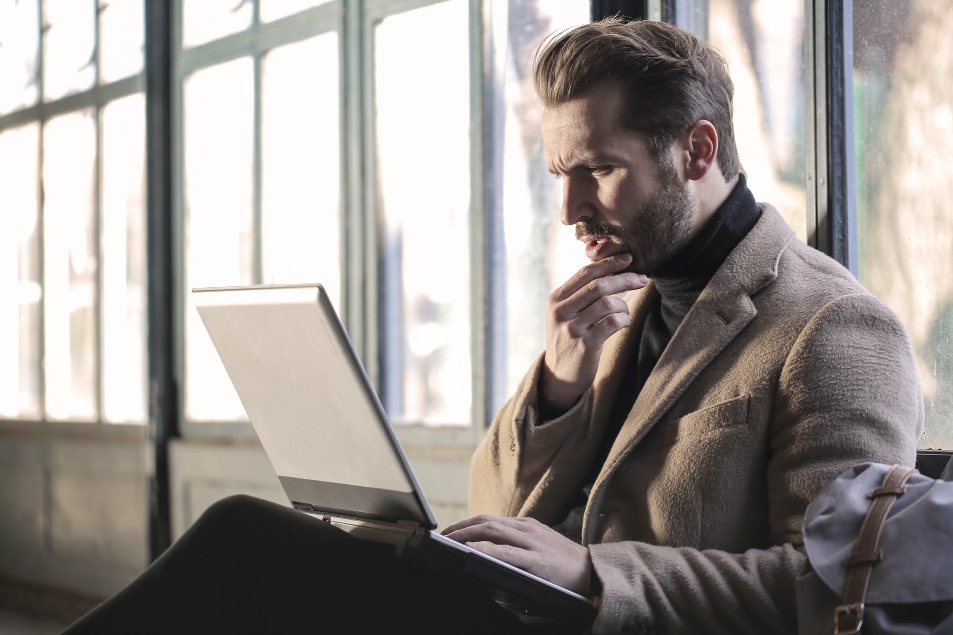 man thinking at laptop - how do I choose the best merchant service provider